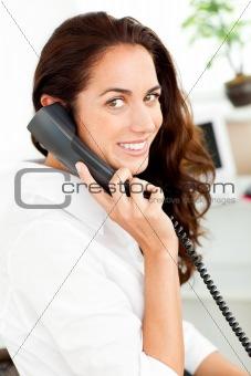 Positive hispanic businesswoman talking on phone