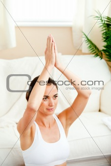 Bright hispanic woman meditating in her living-room