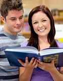 Bright couple of students reading a book