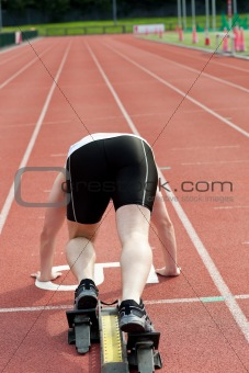 Sporty man waiting in starting block