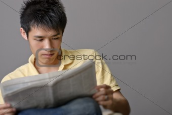 Asian young man reading newspaper
