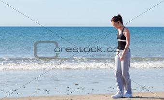 Bright woman standing on the beach and listening to music
