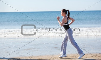 Sporty woman running on the beach and listening to music