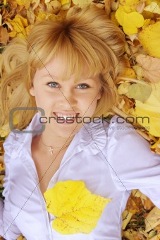 a young girl lies on yellow leaves