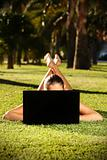 Barefoot woman on a grass with a laptop