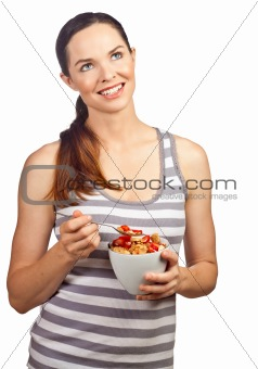 Beautiful young woman eating a bowl of cereal with strawberries