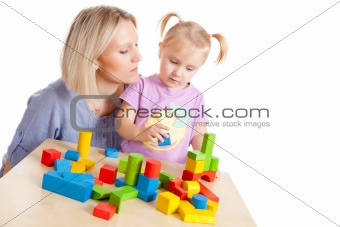 little girl and her mother playing with toy blocks