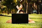 Barefoot woman on the grass hiding behind her laptop