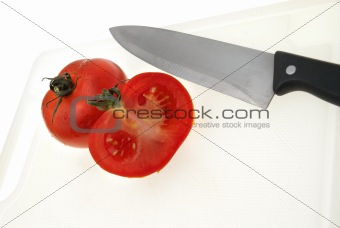 Cutting white plastic board with a knife and tomato