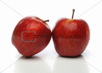 A pair of red apples with drops