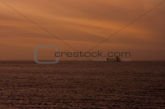 Cargo ship anchored at sunset