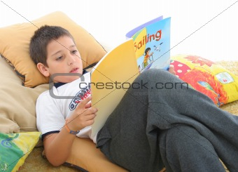 Boy reading a book on the floor