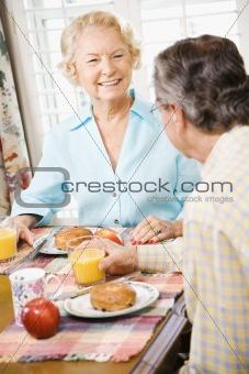Mature couple eating breakfast.
