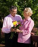 Mature man presenting flowers.