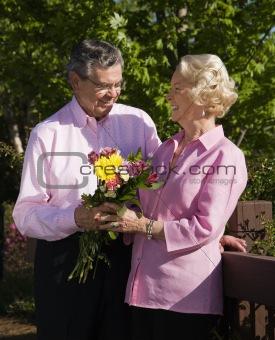 Mature man presenting flowers.