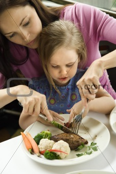 Mom helping daughter cut food.