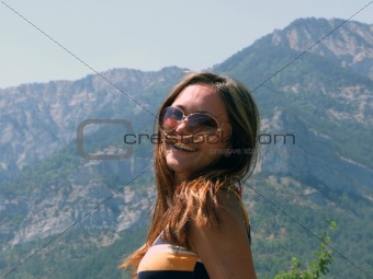 Portrait of the smiling beautiful girl on a background of mounta