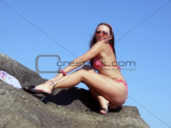 The sexual girl sits on a rock on a background of the sky