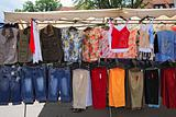 a market stall offering various clothes and textiles