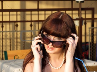 A smiling girl in sunglasses talks by a mobile phone2