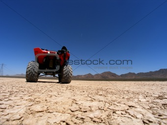 ATV Adventure on dry lake bed against clear blue sky