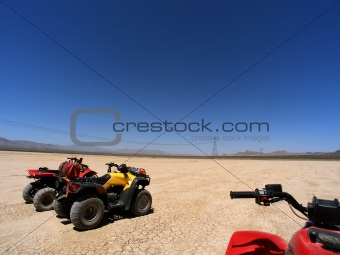 ATV adventure on dry lake bed against clear blue skies