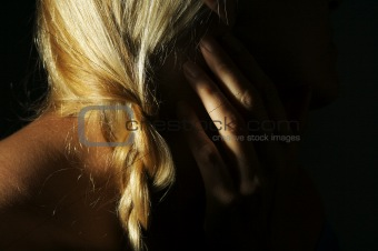 Abstract dramatically lit image of woman's shoulder, hand and blond hair.