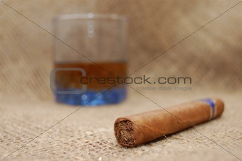 Cuban cigar and glass with wiskey on sackcloth