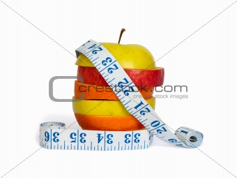 Slices of apples and orange as one fruit and a measuring tape