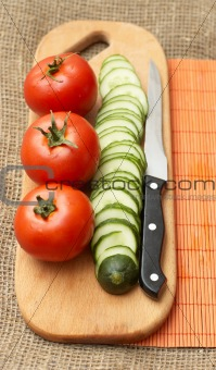 Tomatoes, cucumber and knife on kitchen board