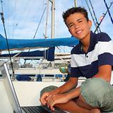 boy teen seat on boat marina laptop computer