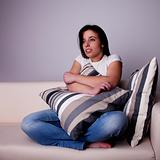 beautiful young woman,  on the couch watching TV, scared.