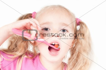 Little cute girl in studio brushing teeth
