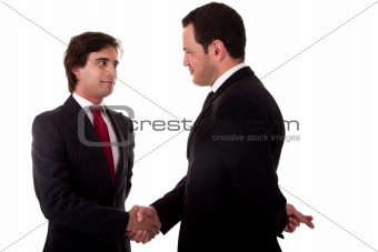 two businessmen shaking hands, and one businessman with his fingers crossed behind his back and smiling