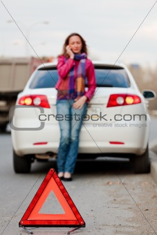 Woman calls to a service standing by a white car