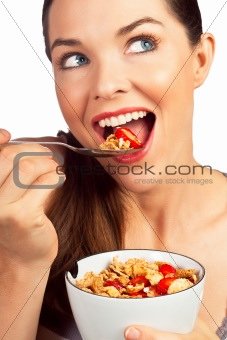 Beautiful young woman eating a healthy bowl of cereal with straw