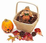Scarecrow doll in basket of cones isolated on white