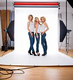 three young female models in casual clothing standing in photographer studio