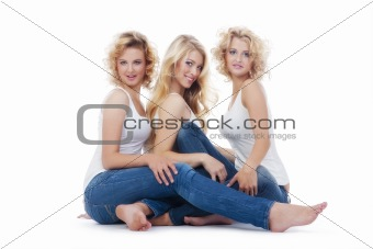 three young women in casual clothing sitting- isolated on white