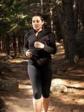 Young woman running in woods, outdoor background