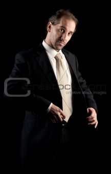 businessman buttoning jacket, getting dressed, on dark background