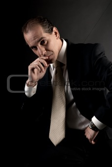 adult businessman serious thinking sitting on dark background