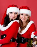 Two women in dressed as Santa, with shopping bags .