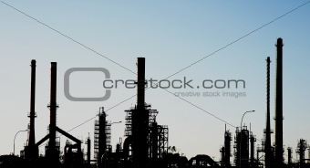 Silhouette of an oil refinery with chimneys