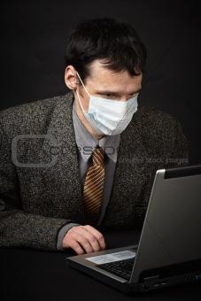 Man in medical mask diagnoses computer