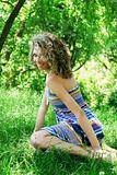 Beautiful young woman sitting on grass