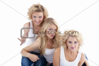 three young women sitting on the floor, looking up- isolated on white