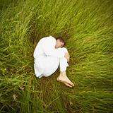 Man lying on grass in fetal position