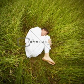 Man lying on grass in fetal position