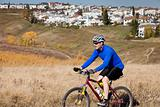 Man mountain biking in park near residential area